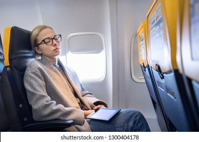 Tired blonde casual caucasian woman wearing glasses, holding digital e-reader, napping on seat while traveling by airplane. Commercial transportation by planes.