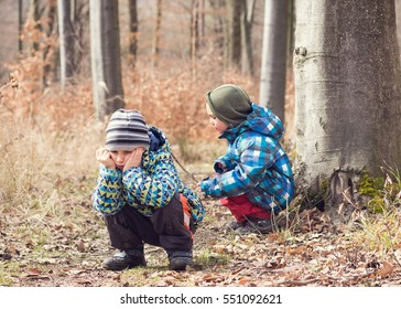 Tired or bored child or children resting in forest on nature walk