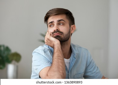 Tired bored man looking in distance, sitting at home or office desk, sleepy freelancer or student feeling lazy, lack motivation, thinking about routine monotonous job, close up