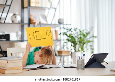 Tired bored school kid sitting at desk at home with head on opened book and holding help sign over his head
