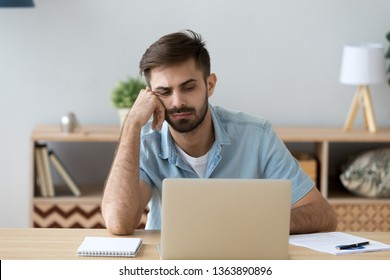 Tired bored student or employee working with laptop, doing boring routine monotonous job, looking at screen, lazy sleepy man feeling exhausted, lack motivation, distracted, sitting at workplace