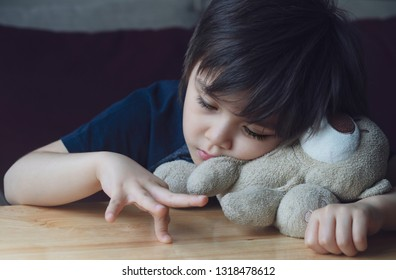 Tired boring boy playing his fingers on wooden table, Emotional parotrait of kid playing on his own while waiting for parent, Lonly child laying his head one teddy bear and looking at his fingers.