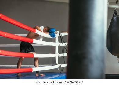 Tired boxer resting in boxing ring, head on gloves. Break in battle