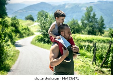 Tired boy on dads shoulder looking down. Father and son bonding. Father is looking lost in nature,while caring son on his shoulders. Cute boy holding world map in hands and sitting on fathers shoulder
