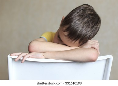 tired boy sits on a chair. boy falls asleep sitting on a chair. He dropped his head in his hands and closed his eyes in weariness and boredom
