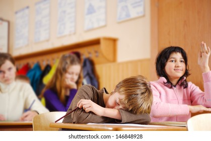 Tired boy is sleeping during school lesson