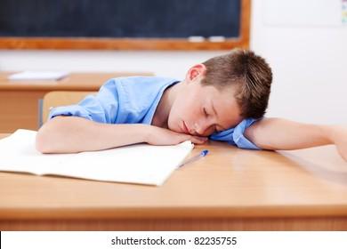 Tired boy sleeping on table in classroom