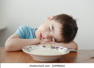 A tired boy sleeping over his morning plate of porridge