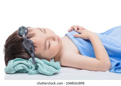 A tired boy sleeps after playing in the pool.