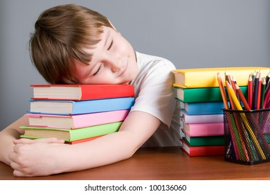 Tired boy sleeps on the books on a gray background