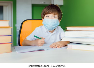 Tired boy studying at home in a protective face mask during CoVid-19 quarantine, distance learning online with a laptop, a child doing homework for school. Schoolboy stayed at home.