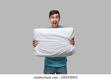 Tired brunet man in a blue tee shout holding white pillow isolated over grey background. Resting after long day.
