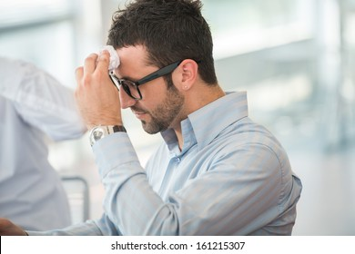 Tired business man with glasses wiping his forehead