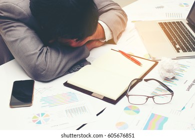 tired business man sleeping on desk with report paper document, pen, laptop and glasses at work, after working all day all night.