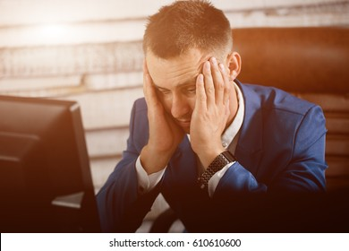 Tired business man at workplace in office holding his head on hands. Sleepy worker early in the morning after late night work. Overworking, making mistake, stress, termination or depression concept