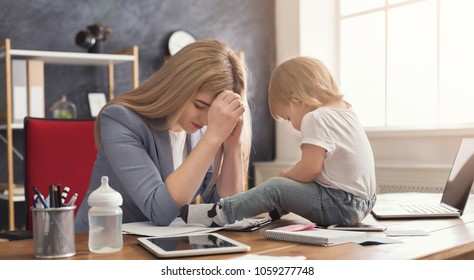 Tired business mom working in office while her cute baby playing with toys. Business, motherhood, multitasking and family concept.