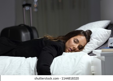 Tired business traveler sleeping on a bed in an hotel room