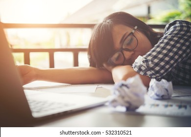 Tired business woman asleep on a laptop while working in her workplace.