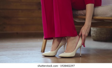 tired business woman takes off her shoes after a long day. swelling of feet after high heels, soft focus. Selective focus.