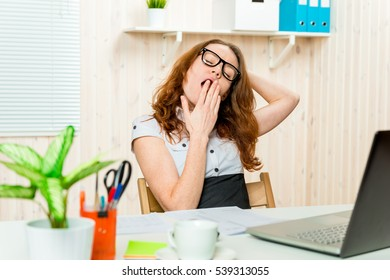 Tired business woman yawning and stretching at his desk in the office
