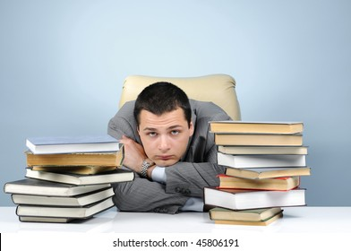 Tired businessman in the books on gray background