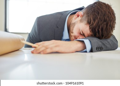 Tired businessman with burnout sleeping on desk