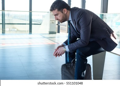 Tired businessman commuter is traveling and is waiting alone