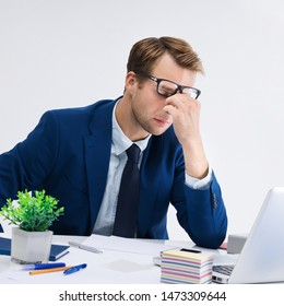 Tired businessman in glasses and blue suit at office. Business, job and education concept shot.