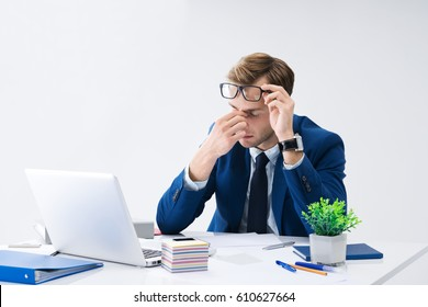 Tired businessman in glasses and blue suit with laptop computer at office. Business, job and education concept shot.