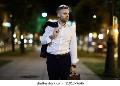 Tired businessman going back home after long working day in the evening