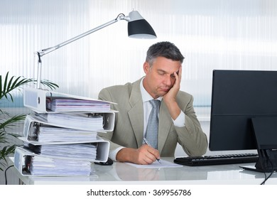Tired businessman with hand on face writing on document in office