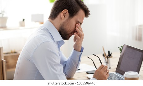 Tired businessman massaging eyes, taking of glasses, exhausted employee suffering from eye strain after long computer work at workplace, blurry vision problem, tension, overworked worker