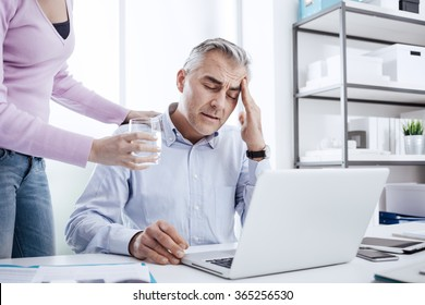 Tired businessman in the office working at desk and having a bad headache, his colleague is giving him a glass of water and touching his shoulder