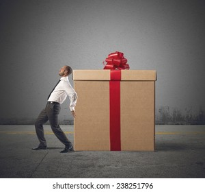A tired businessman pushes heavy great gift