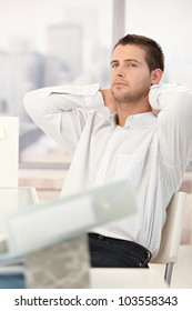 Tired businessman relaxing in chair with hands on back of the neck.