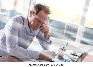 Tired businessman rubbing his eyes sitting in office, light rays effect