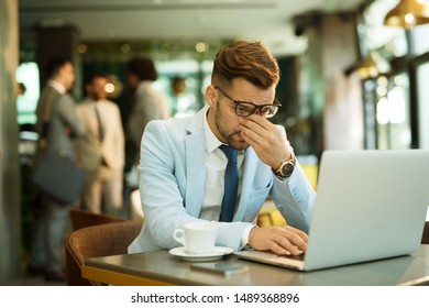 tired businessman sitting in cafe and using laptop