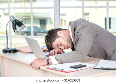 Tired businessman sitting in the office and working on laptop. Businessman sleep and making successful business.