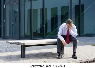 Tired businessman sitting on a bench in front of an office building