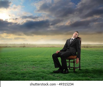 Tired businessman sitting on a chair on a green meadow