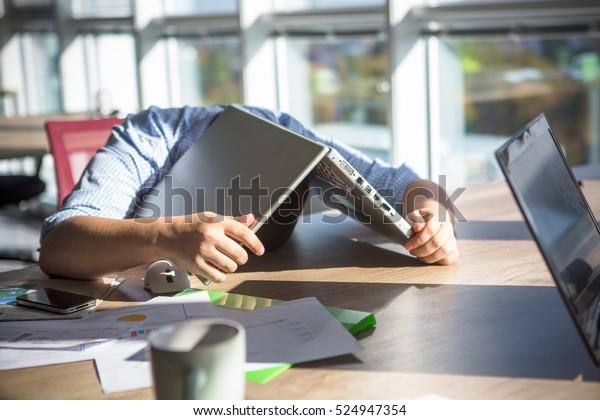 Устал бизнесмен, спящий после тяжелого рабочего дня в офисном интерьере. Человек, лежащий на столе с ноутбуком. Концепция бизнеса.