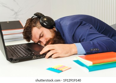 Tired businessman sleeping in office. Bearded man sleeping at his working place. Young business man sleeps on the office desk. Bearded man with his headphones overworked at office.