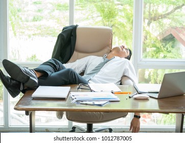 Tired businessman sleeping in the office with his feet up on the desk