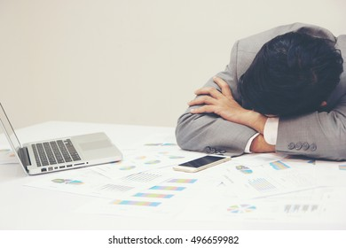 Tired businessman sleeping on the desk in the office