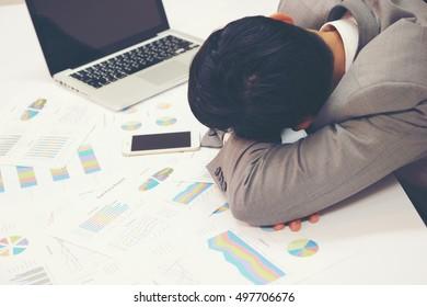 Tired businessman sleeping on the desk