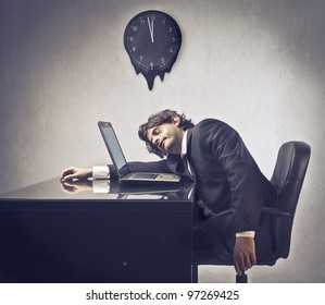 Tired businessman sleeping on his laptop with clock in the background