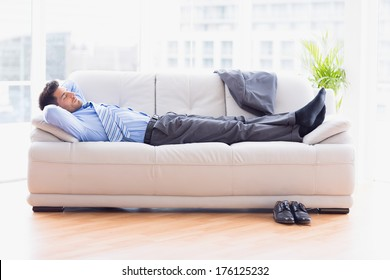 Tired businessman sleeping on a sofa in the office