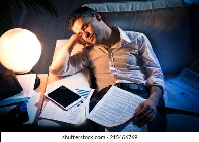 Tired businessman sleeping on sofa at home surrounded by paperwork.