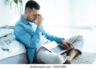Tired businessman struggling with project at home