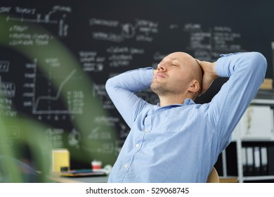 Tired businessman taking a moment to de-stress leaning back in his chair with his hands behind his head and eyes closed